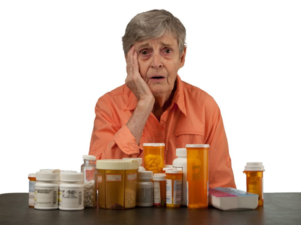 An elderly woman with medications looking overwhelmed